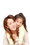 Mère japonaise donnant à sa fille le ferroutage Images libres de droits