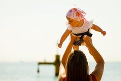 Mère jouant avec la chéri sur la plage photos libres de droits