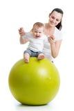 Mère jouant avec le bébé sur la boule d'ajustement Photos libres de droits