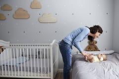 Mère jouant avec le fils nouveau-né de bébé se trouvant sur le lit dans la crèche Photographie stock libre de droits