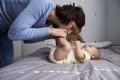 Mère jouant avec le fils nouveau-né de bébé se trouvant sur le lit dans la crèche Photos libres de droits