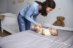 Mère jouant avec le fils nouveau-né de bébé se trouvant sur le lit dans la crèche Photo stock