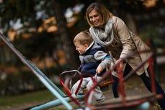 Mère jouant avec le fils sur le caraousel photographie stock