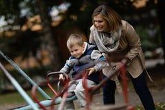 Mère jouant avec le fils sur le caraousel image stock