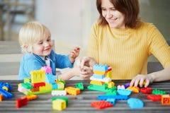 Mère jouant les blocs colorés de construction avec son fils photographie stock libre de droits