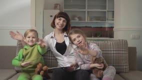 Mère joyeuse et deux enfants s'asseyant sur le sofa et saluant la caméra Vacances de famille banque de vidéos