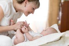 Mère joyeuse jouant et faisant la gymnastique son nourrisson de bébé Image stock