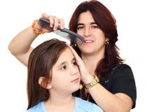 Mère latine se peignant le petit cheveu de descendant Photo stock
