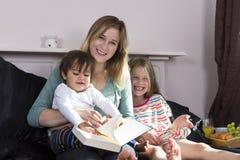 Mère lisant aux enfants dans le lit photo stock