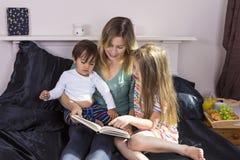 Mère lisant aux enfants dans le lit images libres de droits