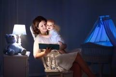 Mère lisant un livre au petit bébé image libre de droits