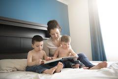 Mère lisant un livre avec ses garçons de deux childs dans la chambre à coucher photos stock