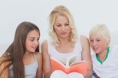 Mère lisant une histoire à ses enfants Photos stock