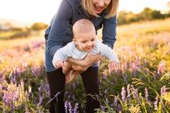 Mère méconnaissable en nature avec le fils de bébé dans les bras Images libres de droits