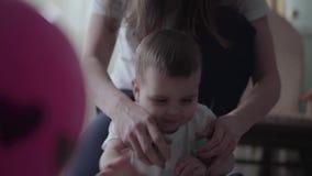 M?re m?connaissable jouant avec son fils de b?b? s'asseyant sur le plancher Femme mettant deux boules essayant ensemble d'obtenir banque de vidéos