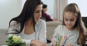 Mère mûre impressionnante avec ses enfants les aidant pour faire quelques devoirs, ils sont très exaltés et excités sur le s clips vidéos
