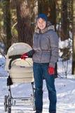 Mère marchant avec la voiture d'enfant en hiver Photographie stock libre de droits