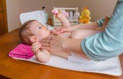Mère massant le corps de son mensonge de bébé Image libre de droits