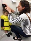 Mère mesurant la taille de sa fille Image libre de droits
