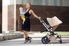 Mère moderne à la mode sur une rue de ville avec un landau. Jeune mère photos stock