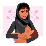 Mère musulmane dans le costume national tenant son enfant nouveau-né de bébé dans son allaiter de bras Image libre de droits