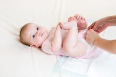Mère obtenant le bébé habillé photos stock