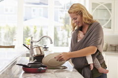 Mère occupée avec le bébé dans le traitement multitâche de bride à la maison images stock