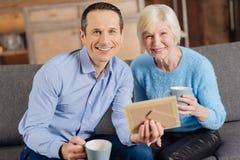 Mère optimiste et fils posant tout en regardant la vieille photo Photo stock