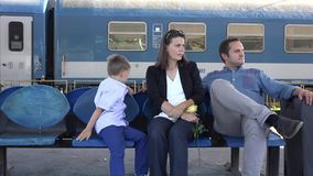 Mère, père et enfant attendant dans la station de train, voyage heureux de famille banque de vidéos