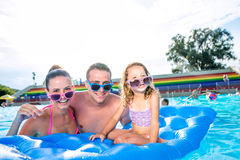 Mère, père et fille dans la piscine Été ensoleillé Photographie stock libre de droits