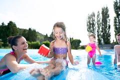 Mère, père et filles dans la piscine Été ensoleillé Photos libres de droits