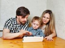 Mère, père et fils de famille regardant le PC de comprimé Images libres de droits
