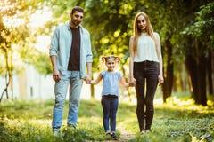 Mère, père et petite fille marchant en parc d'été et ayant l'amusement Images libres de droits