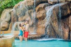 Mère, père heureux et fils de famille détendant sous une cascade dans l'aquapark image stock