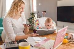 Mère parlant sur le bureau futé de téléphone à la maison Image libre de droits