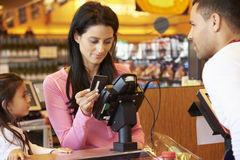 Mère payant des achats de famille au contrôle avec la carte Images stock