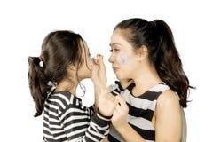 Mère peignant un visage de sa fille Photo stock