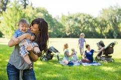 Mère portant le bébé garçon gai au parc Image stock