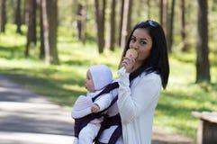 Mère portant le transporteur de bébé infantile Photos stock