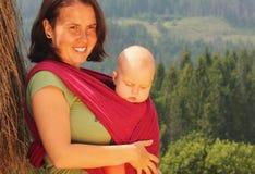 Mère portant sa chéri dans une élingue Photographie stock