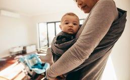 Mère portant son bébé dans un transporteur d'enveloppe de bébé image libre de droits