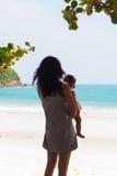 Mère portant un enfant à la mer Images libres de droits