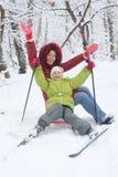 Mère, pose de descendant sur le traîneau avec le ski Images libres de droits