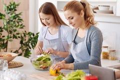 Mère positive et sa fille faisant cuire la salade végétale image libre de droits