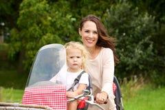 Mère prenant sa fille sur le tour de bicyclette en parc Photographie stock libre de droits