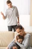 Mère protégeant sa fille contre le père fâché Photographie stock libre de droits