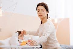 Mère réfléchie guérissant son enfant malade Photographie stock libre de droits