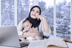 Mère rêvassant tout en travaillant et soignant le bébé Photographie stock libre de droits