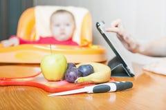 Mère recherchant la recette de la préparation de l'aliment pour bébé Image stock