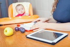 Mère recherchant la recette de la préparation de l'aliment pour bébé Photographie stock libre de droits
